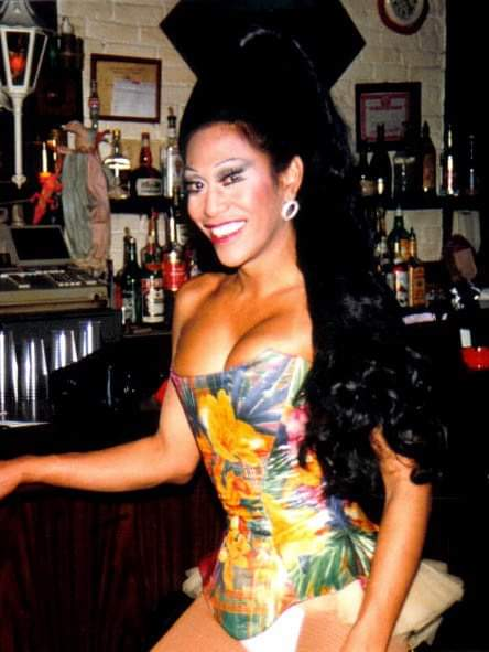 Sina with long black hair down her left side. Colorful strapless dress. Standing in front of a bar.
