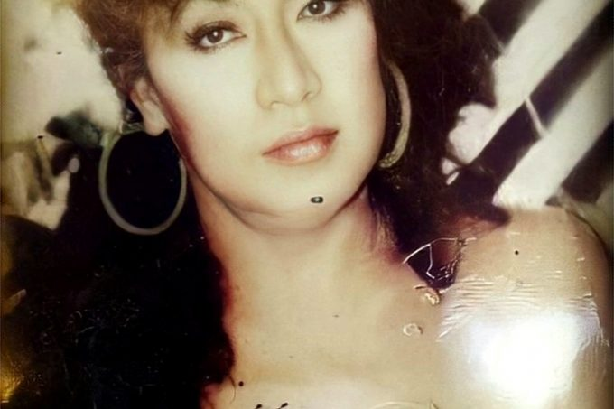 Sepia toned photo of Tanya with quaffed hair, gold hoops and a pink shimmer lip.