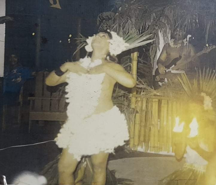 Tanya in a white shirty and top with white flowers in her hair. Dancing on a stage infront of someone holding fire torches.